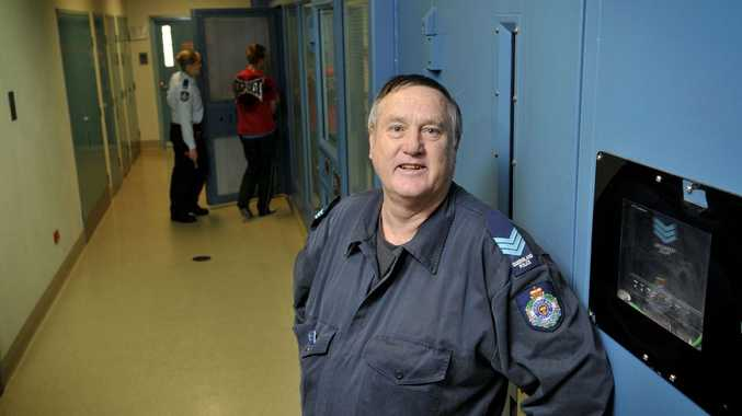 KEEPING WATCH: Toowoomba watch house Sergeant Owen Williams closes the cell door for the last time upon his retirement after 40 years a policeman.