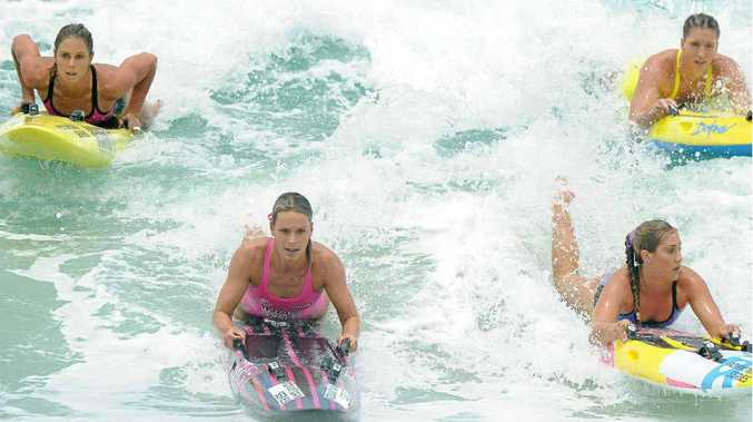 Courtney Hancock, left, and Liz Pluimers lead the field home in the board section at Surfers Paradise yesterday.