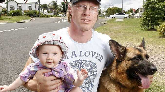 Ken Knebel with his seven-month-old daughter Samara and dog Sina on the street where they were attacked by two big dogs in Ipswich.