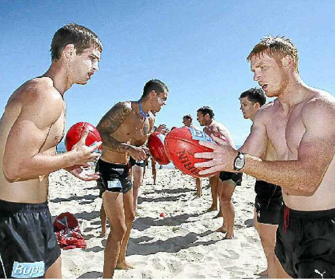 Hawthorn footballers practise handballs during a training session at Mooloolaba.