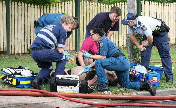 Paramedics attend to a woman who suffered burns in a house fire on Christmas Eve.