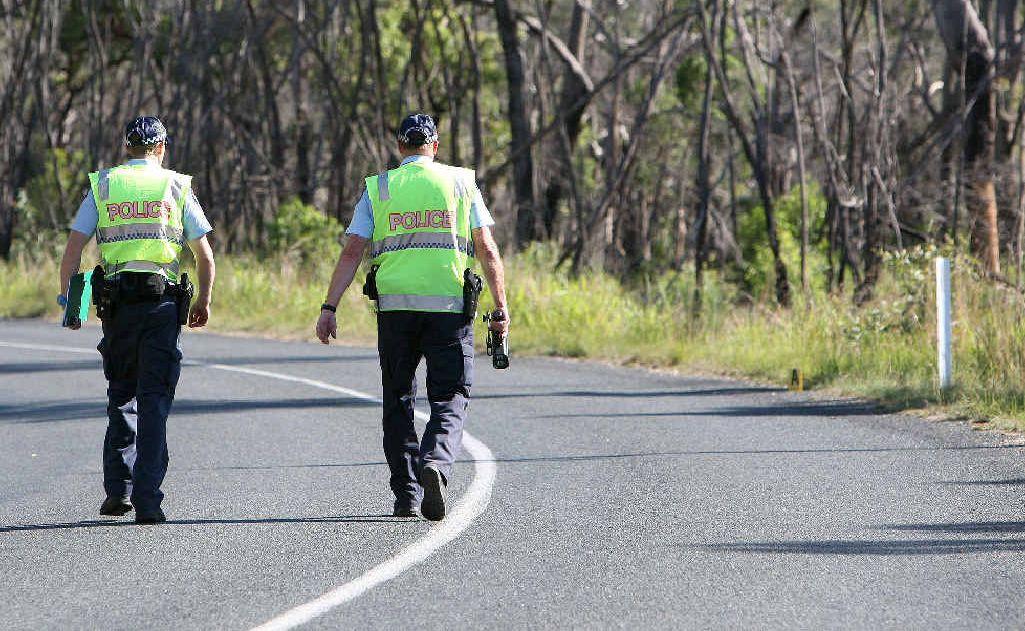 Forensic Crash investigator Matthew Cummins and Sgt Bill Feldman walk to the point where the motorbike left the road to investigate the crash.
