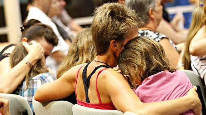 Mums comfort their children as friends and family of the Golinskis gather at The Anglican Church of Noosa yesterday.