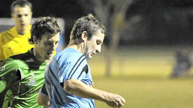 Bundaberg Spirit's Brett Kitching controls the ball away from Whitsunday Miners' Jamie White in a match this year.