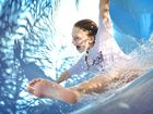 Amy Howard, 10 of Golulburn makes a splash rounding the final turn of the waterslide in the warm weather at the Grafton Aquatic Centre waterslide.