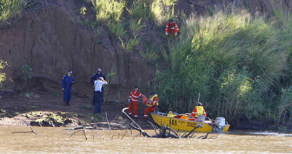 SES volunteers and police search the Brisbane River at Goodna after receiving reports of a murder.
