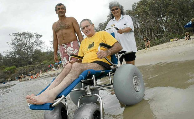 Ted Kabbout of the Disabled Surfing Association, with his partner Andrea and Owen Danvers, using a beach wheelchair at Brunswick Heads last year.