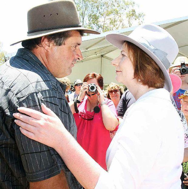 Prime Minister Julia Gillard greets a local at the Gatton commemorative flood service today.