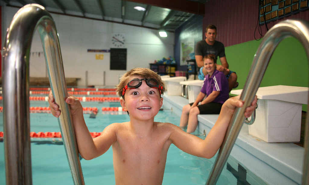 Natan Gooch is back in the pool under the watchful eye of swimming instructor Di Manzelmann and his dad Barwon Gooch after almost drowning when he blacked out during squad training at the Pat Wright Swim School.