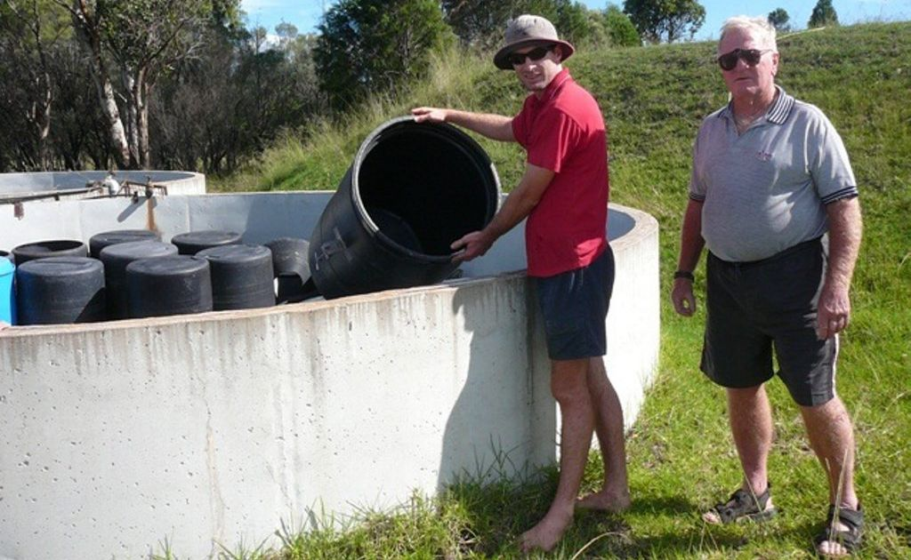 Nick Donges showing Roger Warwick District Recreational Fish Stocking president Roger Martin the drums in which the Murray Cod lay their eggs when induced to spawn. The drums are submerged into a large dam and the cod swim into them to lay their eggs.