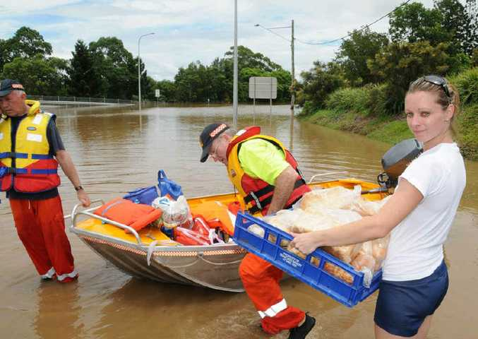 SES volunteers help ferry basic grocery items across a flooded Mary River to stranded Southside residents last year.