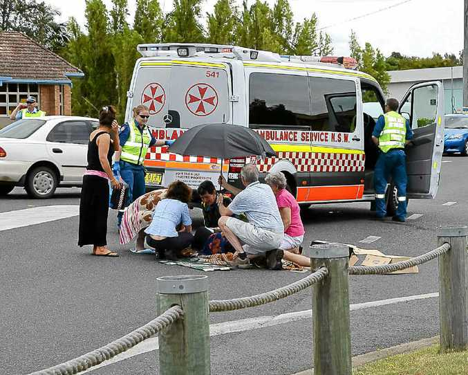 A Woodburn man is attended to by locals, passers-by and paramedics after being hit by a car on the Pacific Highway at Woodburn yesterday.