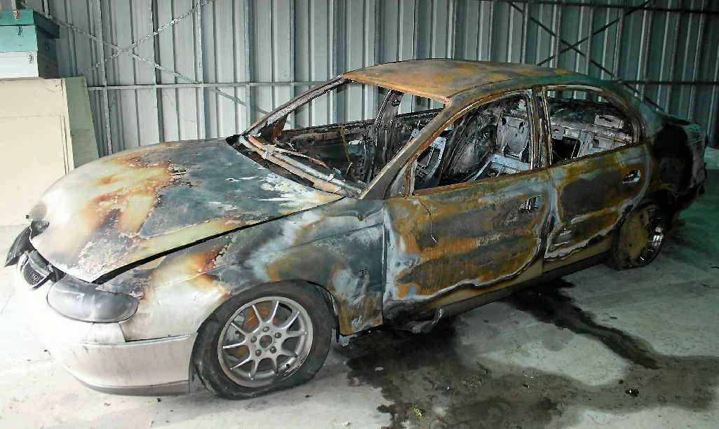 The shell of the Holden Calais torched in Freestone Rd on Saturday night.