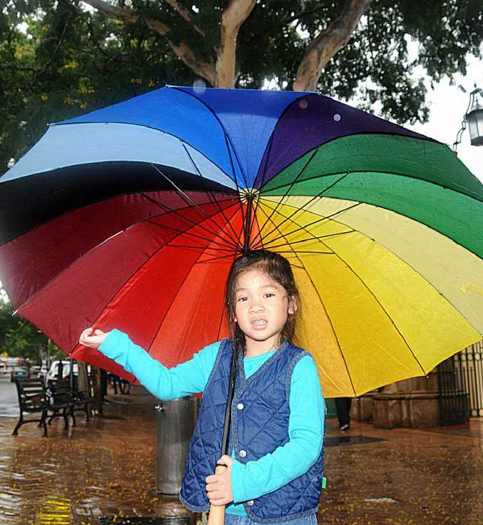 """Yen-Yen To has no intention of getting wet and has a """"rainbow umbrella"""" that will ensure she stays dry."""