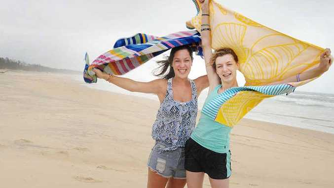 Brisbane's Melanie Dunn and Kate Newman brave the wild weather during their visit to Rainbow Beach.