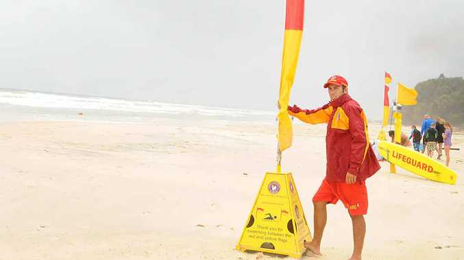 Lifeguard Sam Murray surveys the blustery and potentially dangerous conditions at Rainbow Beach yesterday.