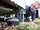 Brian Kneebone from Common Courtesy Pest Control places a tamper-proof bait station under an outdoor shed. Twelve months after the floods, rat infestations remain a common problem in Ipswich.