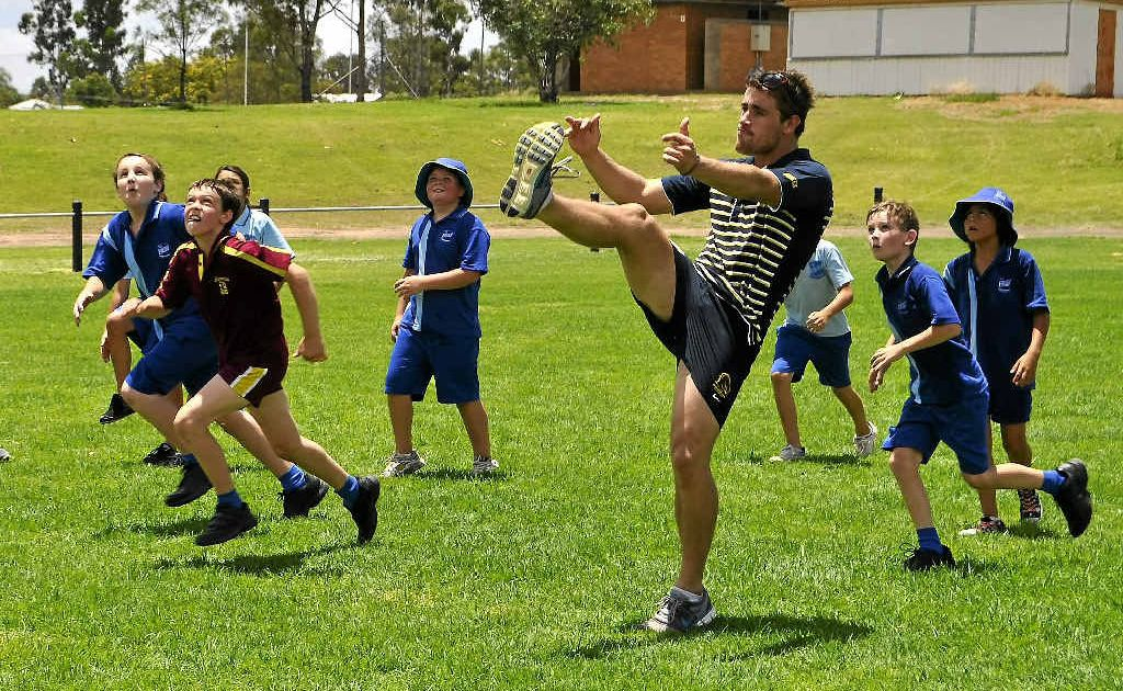 Broncos hooker Andrew McCullough, kicking at a Dalby coaching clinic, will play in the Warwick cricket carnival for Max's XI.