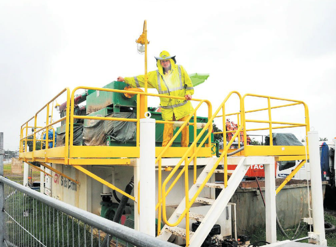 An Energex worker operates the boring rig that is drilling under the Bruce Highway to connect Gympie's upgraded power network with 33,000 volt power cables.