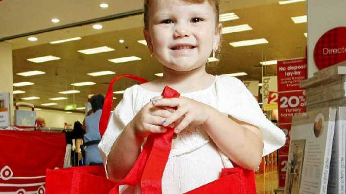 Emma Gibson, 3, of North Booval tries out the new Target biodegradable and reusable shopping bags.