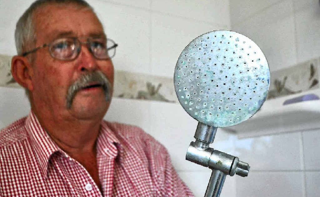 Pratten resident Robert Holt compares a shower head used when the home was connected to the town's water supply with the new one installed since they put down their own bore.