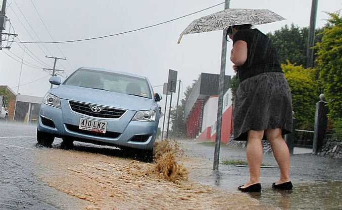 Navigating Nash St was a daunting task for this resident as torrential rain fell yesterday.