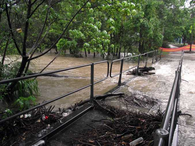 Petrie Creek at Nambour washes over a footbridge to Quota Memorial Park.