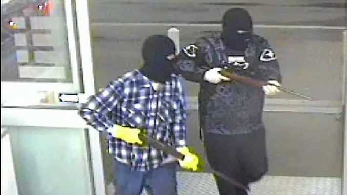 Two men armed with rifles during the Oaks robbery.