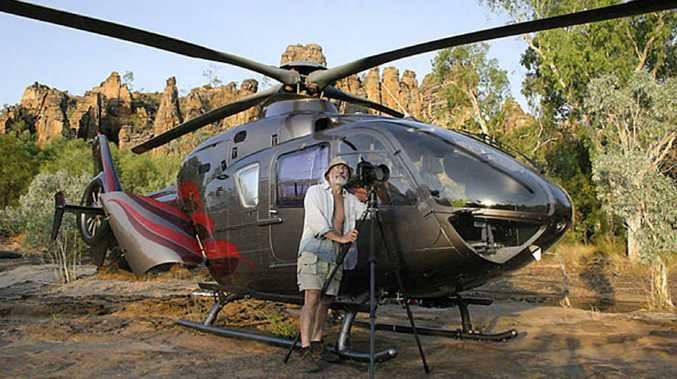 Photographer Richard Green with the helicopter he flies to access some of the most beautiful places in the country.