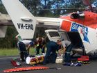 Paramedics treat one of the injured from the crash on the Steve Irwin Way at Beerburrum yesterday afternoon. Photo: AGL Action Rescue Helicopter