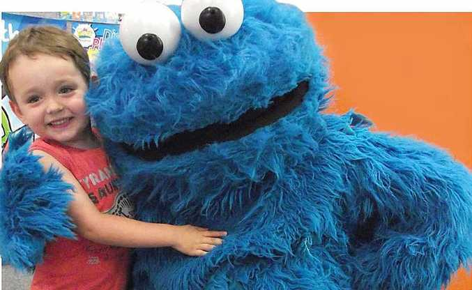 Three-year-old Chace Sims gets a hug from the Cookie Monster at the Maroochydore Library.