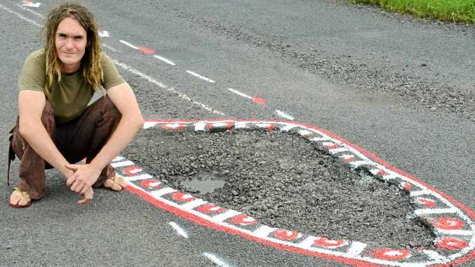 Aaron Gibbs of Lismore pictured on Nimbin Rd at Goolmangar with the pothole that caused more than $3000 of damage to his father's car.
