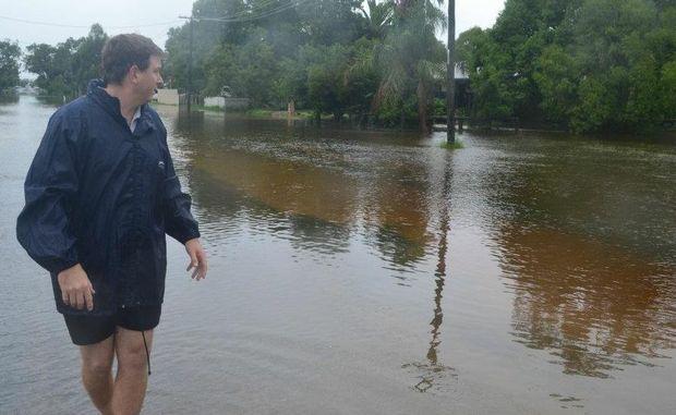 Roma resident Steve Hogan checks the rising water at Gregory St at Roma.