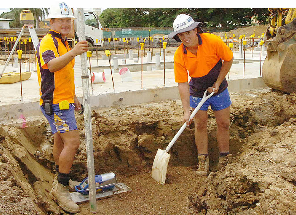 Plumbers Kyle Greaves and Mick Scott dig trenches around the new building's foundations.