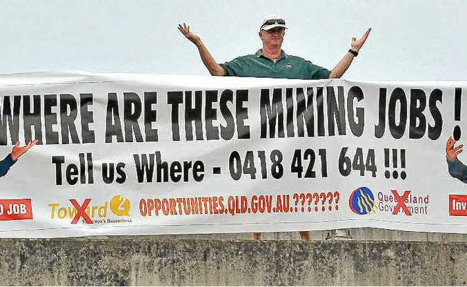 A SIGN OF HIS TIMES: Mark Freeman stands behind the sign he erected yesterday at a busy Sunshine Coast overpass, revealing his frustration at not being able to get a job in the booming mining industry.
