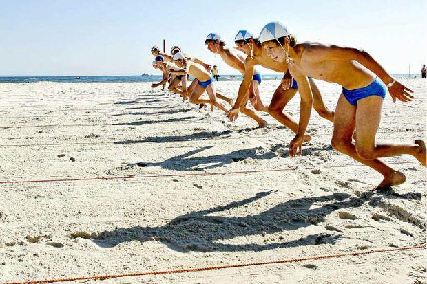 Beach sprinters at Byron Bay junior surf lifesaving carnival warm-up for local championships.