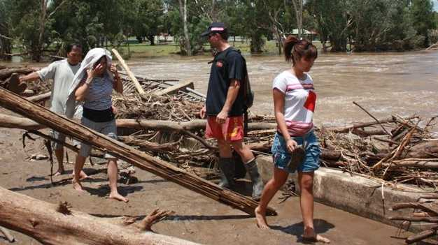 An SES worker helps a family stranded at the wrecked Mitchell bridge cross into town over the still swollen Maranoa River