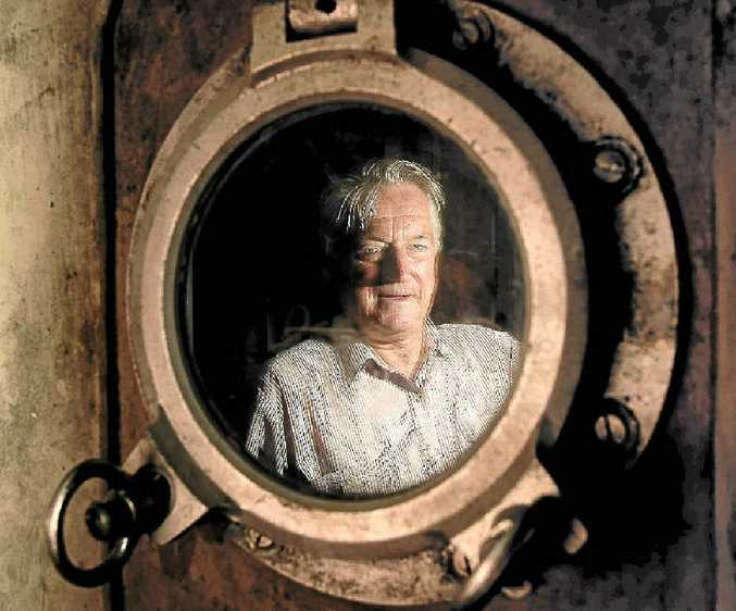 Ray Evans looks through a porthole from his vast collection.