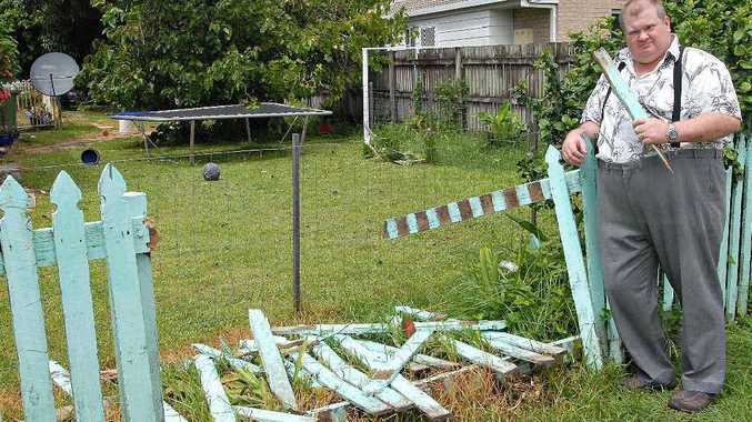 Alf Maher stands beside his front fence, which was damaged when his car was shunted into it by an out of control utility.