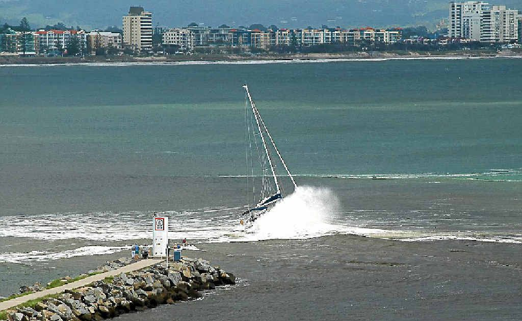 A yacht has difficulty crossing the mouth of the Mooloolah River after the sand returned following recent dredging.