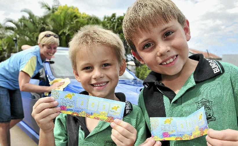 Caiden Brown and Bailey Brown get their loyalty cards from Puddles Carwash owner Karen Rann as part of the Reef Ranger Program to help care for the environment.