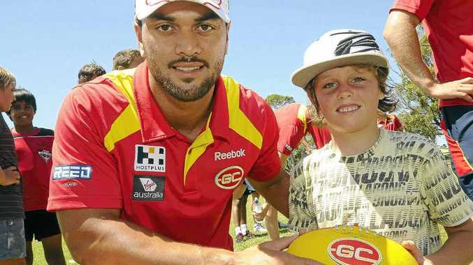 Oscar Vickarage, 8, of Alstonville getting some tips from Gold Coast Suns player Karmichael Hunt at the AFL super clinic at Ballina High School.