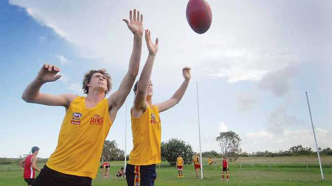 Jacob Lowe and Hayden Lange show off their Aussie Rules skills during a Gold Coast Suns academy camp.