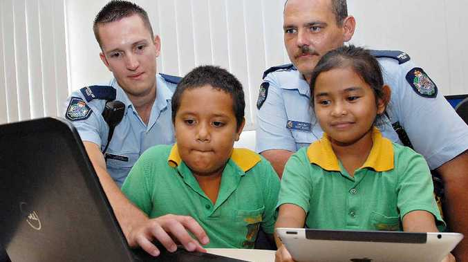 Mackay Central School students Marques Soper and Juliana Delmo learn more about cyber safety from constables Matt Redmond (left) and Scott Black.