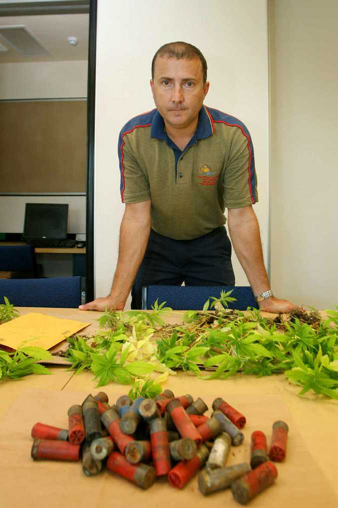 Detective Senior Constable Alex Nezic with a haul of marijuana seedlings and ammunition seized from a Hidden Valley, Yeppoon, property.