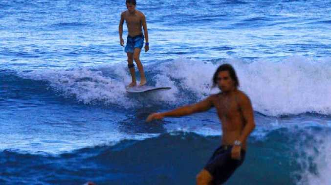 Surfers at Moffat Headland chased waves as the full moon rose last night.