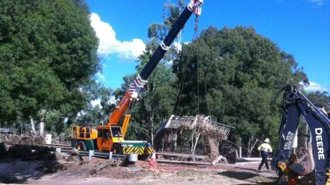 Workers clear the Warrego River Bridge in Mitchell yesterday.