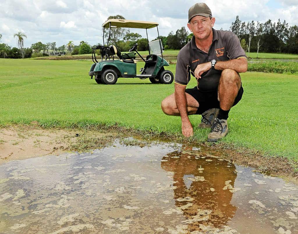 Oakwood Golf Club greenkeeper Wayne Stacpoole with a waterlogged bunker.