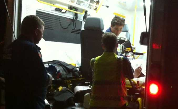 Ambulance crew treat a man who was knocked off his bike by a  kangaroo on his way home from night shift.