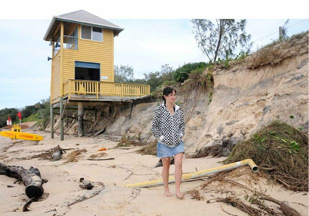 SAND EROSION: Nicole Watts walks along a different-looking beach at Rainbow. Huge seas back in 2009 took thousand of tonnes of sand out to sea, leaving 3m-high sand cliffs and undermining the Surf Club tower. Now council hopes to safeguard the beach against erosion.